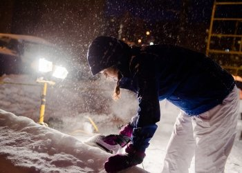 A female student irons the side of a snow statue while snow falls.