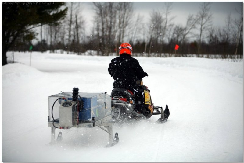 A snowmobile tows a mobile acoustics and emissions testing device mounted on two ski-like runners.