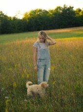 A young woman stands in a field looking down at a puppy.