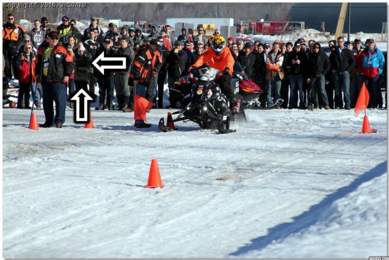 A snowmobile races down an obstacle course and two arrows point to a young woman in the crowd.