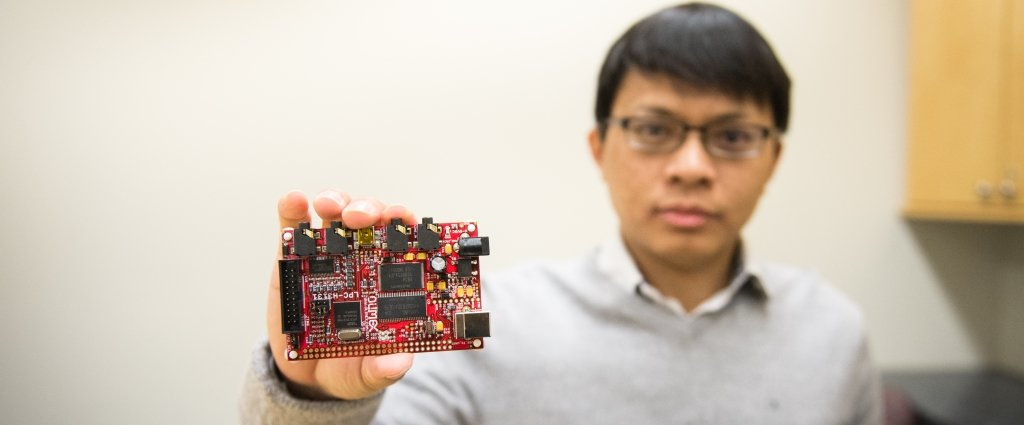 A man wearing glasses holds a red circuit board the size of a deck of cards.