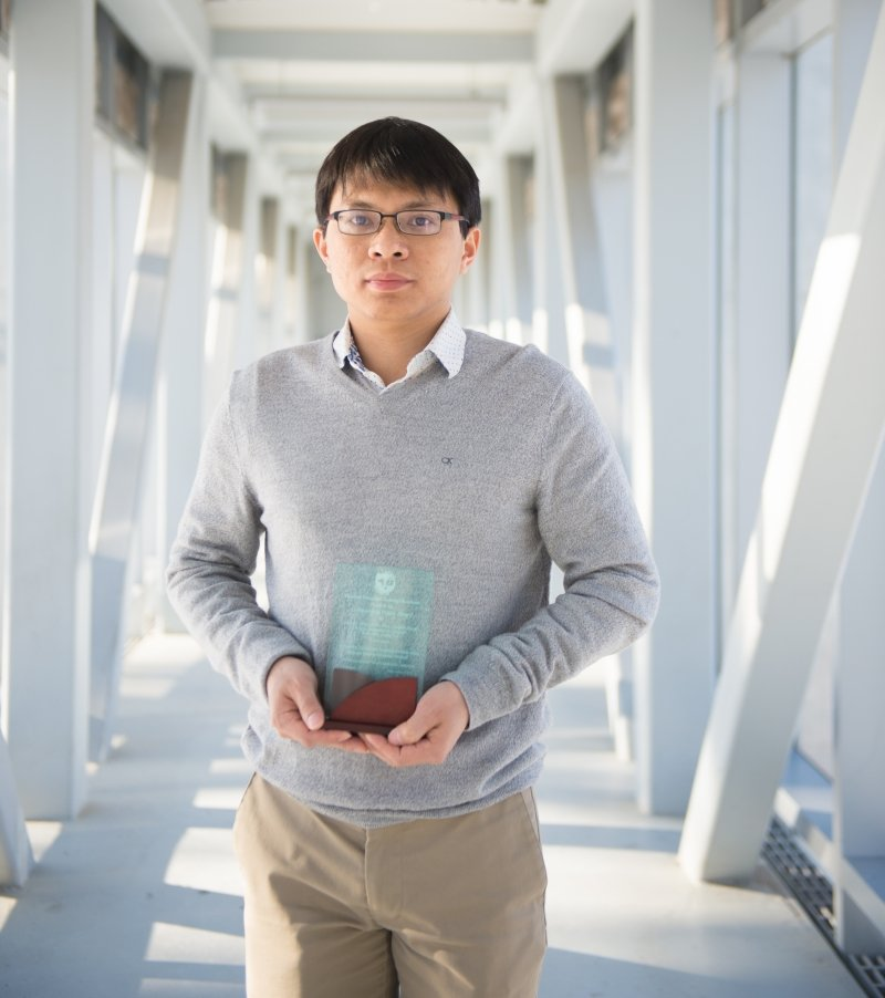 A man wearing glasses holds a glass award plaque.