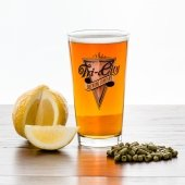 A pint glass full of beer sits beside a sliced lemon and a pile of pelletized hops.
