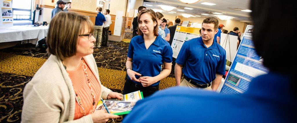 A young woman and man in blue shirts in front of a poster in a ballroom exhibit talk to a woman holding a Design Expo booklet and clipboard