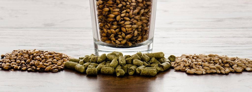 A pint glass filled with malt and piles of mile and pelletized hops in front of the glass on a counter top.
