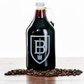 A growler of dark beer with coffee beans scattered in front of it.
