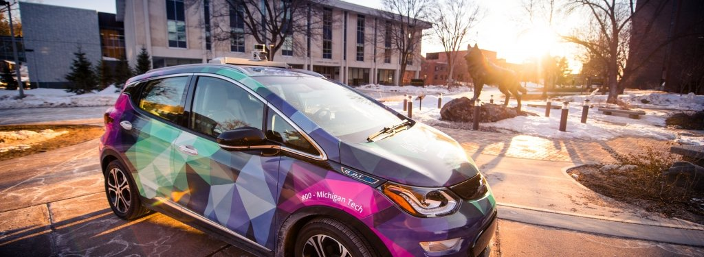 A car with a bright wrap of aurora borealis colors is backlit by the setting sun on Michigan Tech's campus