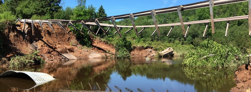 Washed-out bridge supports hang suspended over a river. A washed-out culvert floats in the water.