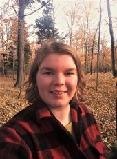 young woman in flannel shirt in the woods