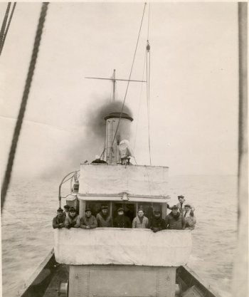A black and white 1918 photo of men on the bridge of a ship steaming out to sea with lake superior in the background