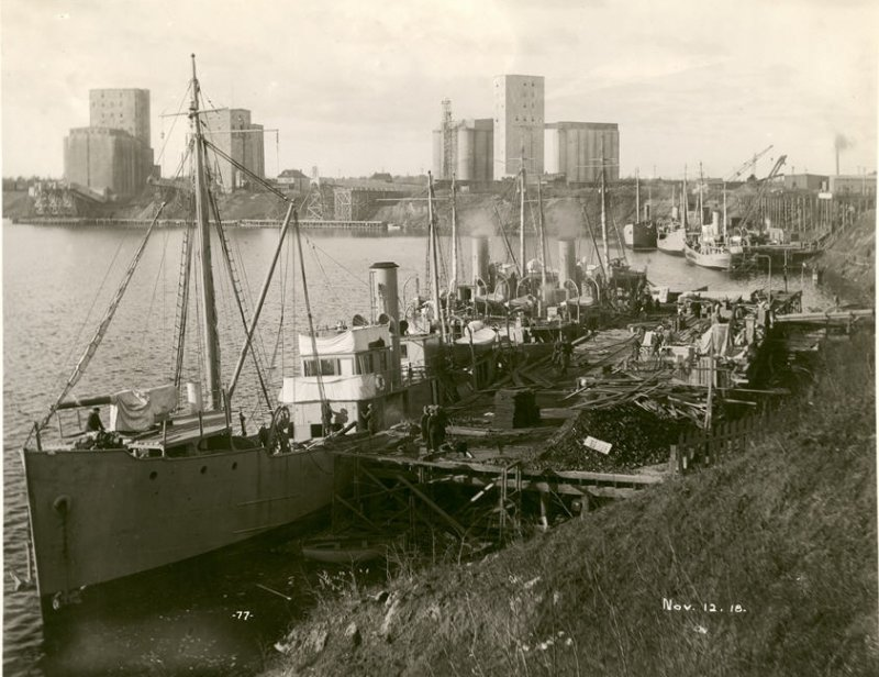 Newly built and outfitted minesweepers at the dock in a black and white photo from 1918 in a harbor on lake superior