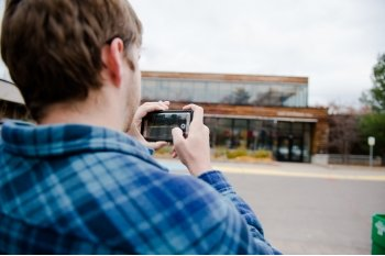 A young man in a blue plaid shirt records video on his phone, his back is to us, he is outside facing a building with windows.