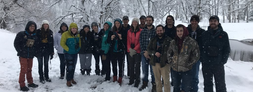 class of students standing in snow next to a creek
