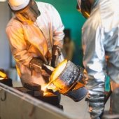 people in safety gear pour molten metal