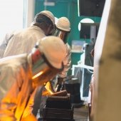 people in safety gear work with molten metal