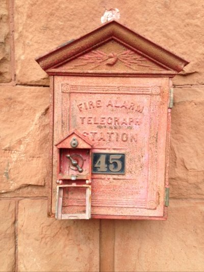 antique fire alarm with faded red housing