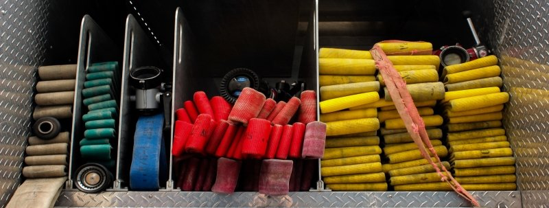 brightly colored fire hoses folded in the back of a firetruck