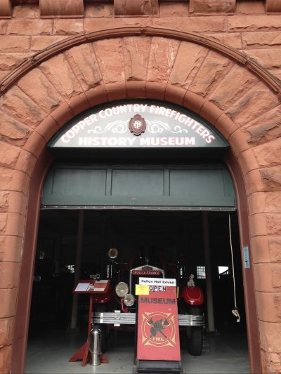 sandstone archway with antique firefighter equipment in the doorway