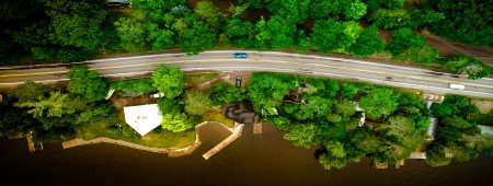 drone image overhead of road with blue car and trees
