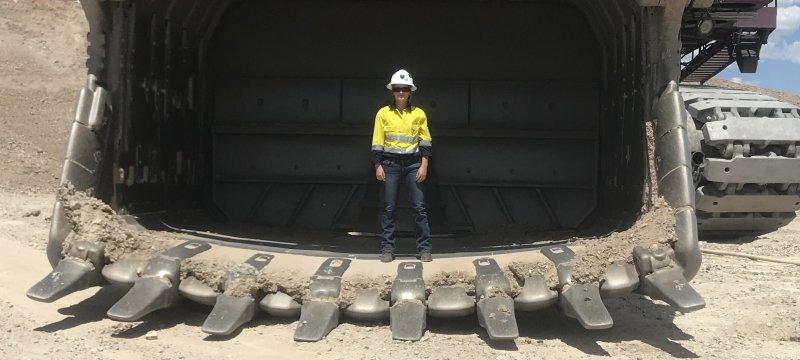 woman in a hard hat standing next to a 20-foot tall mining truck