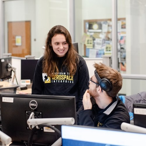 a female student with Michigan Tech Aerospace on her shirt talks to a male student sitting at a monitor wearing head phones like ear muffs
