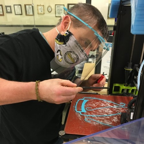A man with a Michigan Tech Huskies face mask and a face shield on campus with a 3D printer printing PPE face shields.