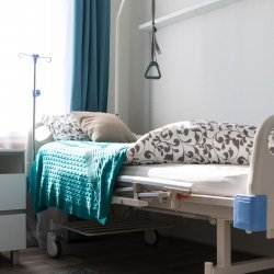 a home hospital bed with handhold, a colorful graphic geometric quilt and a window in the background.