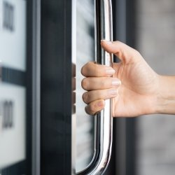 hand cripping a silver handhold on the door of a commuter vehicle with blurred background