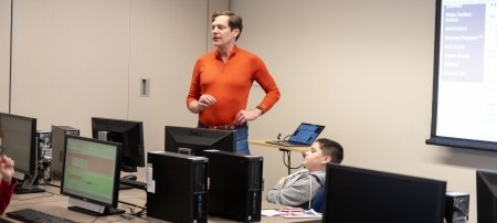A man teaching in front of a computer class in a bright orange shirt with a young       boy facing him and computer monitors with a white screen in the background