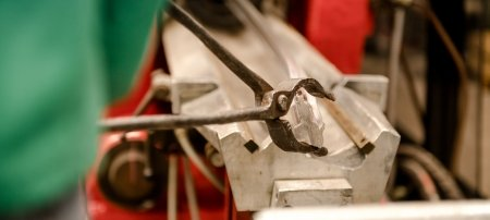 A person uses a pair of metal tongs to pull an aluminum rod through an extruder machine.