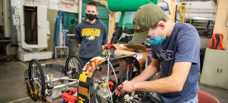 Students wearing face masks and safety goggles work on an engine in a garage space,       one with his hands on the engine and the other wearing a Michigan Tech sweatshirt       looking on next to the wheels. There is a roll of green gauze behind them in a shop       with a fan and industrial equipment in the background.
