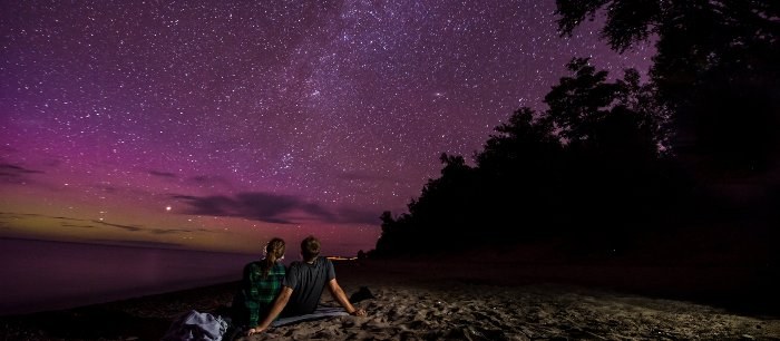 Two people sitting under a purple night sky full of stars.