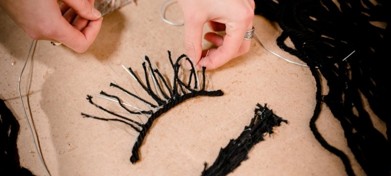 Art student putting together a piece of art with wire and yarn.