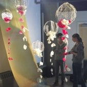 Two students standing inside the Rozsa Gallery discussing an exhibit of a long piece of fabric that is draped from the ceiling with a river and sunset painted on it. Above them is an installation with balloon-shaped pieces made with wire and simulated flower petals.
