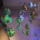 An installation hanging from the ceiling of aluminum foil crafted into flower petals, with light shinning on them to create colors.