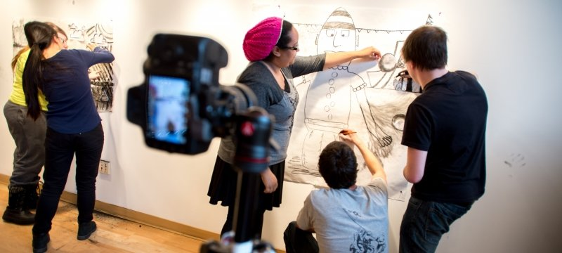 Faculty works with students on a large drawing on a wall with a camera looking on.