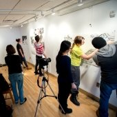 Students work on large drawings on the studio walls with a camera recording.