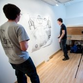 Two students work on a large drawing on a studio wall while a faculty observes and a camera records.