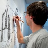 Student works on a pencil drawing on the studio wall.