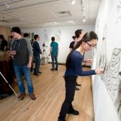 Students work on their drawings on the studio wall while others observe.
