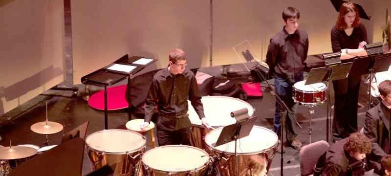 Student in a concert band standing in the middle playing large drums while looking a music on a music stand during a performance.