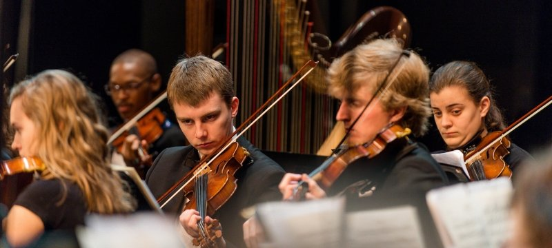 Students performing in the Keweenaw Symphony Orchestra, a closer view of the violinists.