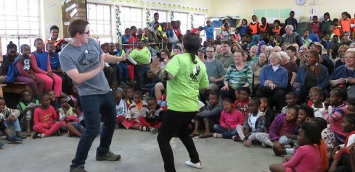 Concert Choir member dancing with a South African girl in front of a large group of onlookers.