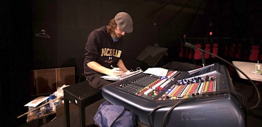 Student sitting, writing, at a sound board inside McArdle Theatre.