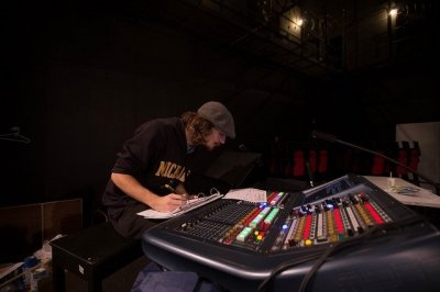 Student sitting at sound board making adjustments