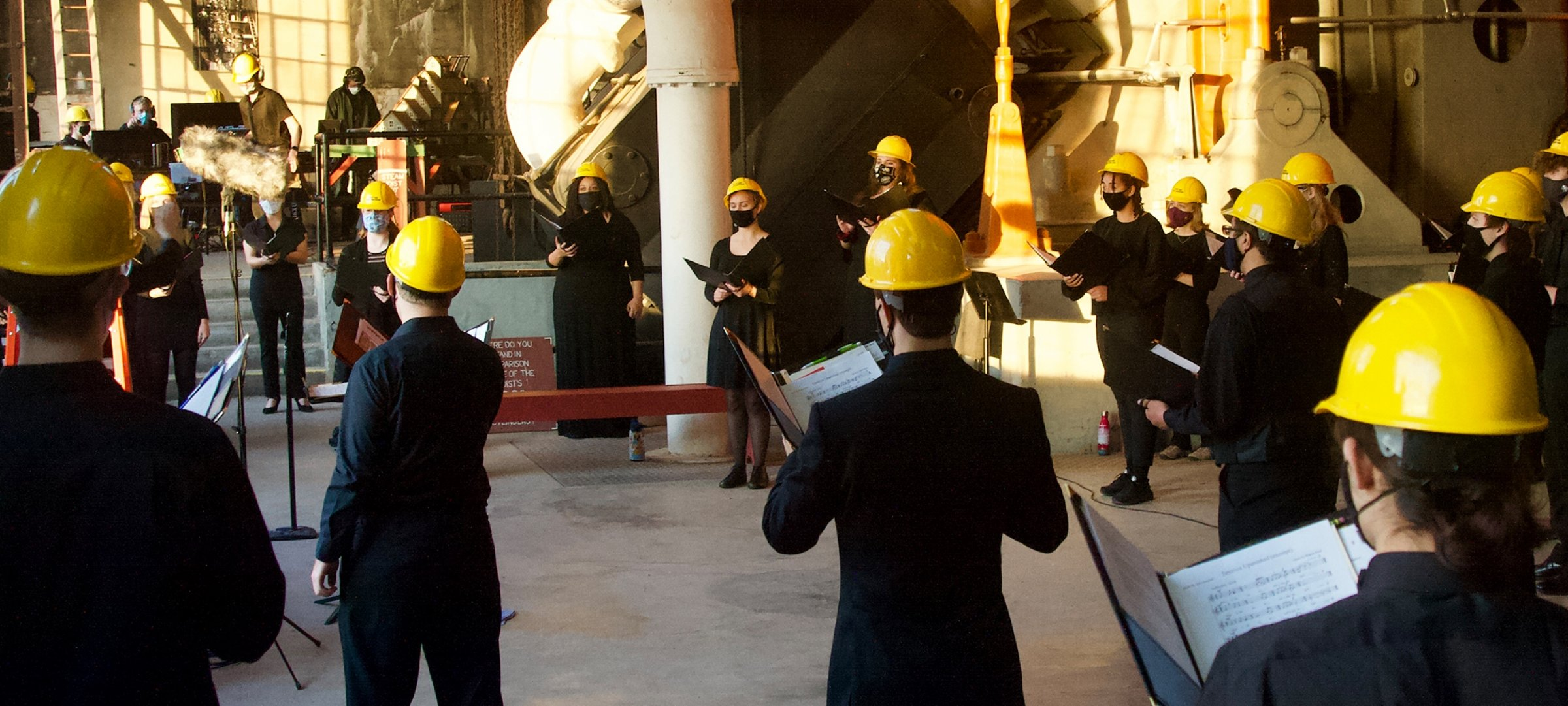 Singers wearing hardhats and face coverings in a Quincy Mine building.