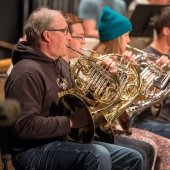 Three members of the Keweenaw Symphony Orchestra play the French horn.