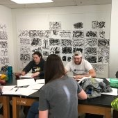 Students sitting around a workbench painting.