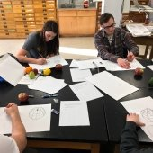 Students sitting around a work table drawing fruit