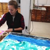 Student working on a painting of swirls and water.